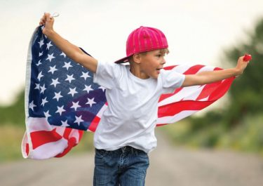 Boy running on country road with flag. Image credit: iStock