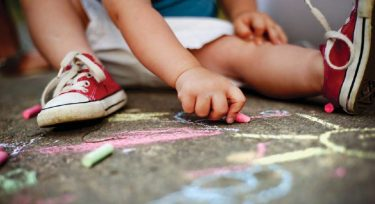 Toddler seated with sidewalk chalk. Image credit: iStock
