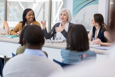 Woman talking on panel at meeting. Image credit: iStock