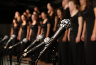 Choir behind microphones. Image credit: iStock