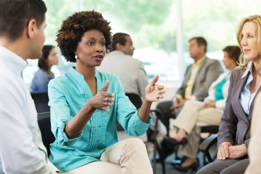 Serious African American woman makes a point during meeting. Image credit: iStock