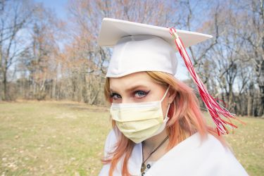 High school woman with mortarboard and mask.Image Credit: iStock