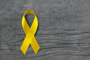 Yellow ribbon symbolic for Sarcoma Bone cancer, Spina Bifida Awareness Month and suicide prevention. Image Credit: iStock