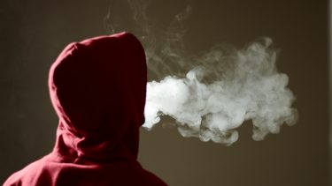 Youth in hood expelling vape smoke.Image Credit: iStock