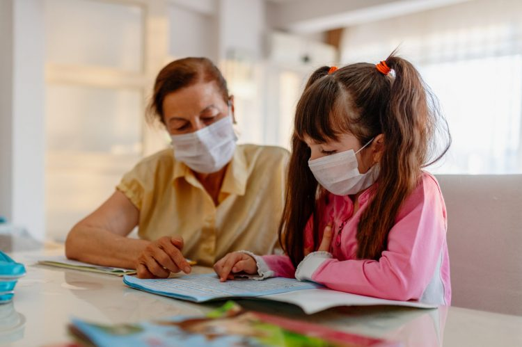 Masked mother and daughter reviewing book.Image Credit: iStock