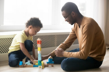 African American father and adorable son building constructor tower. Image credit: iStock