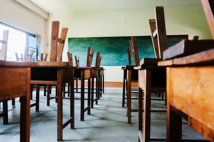 Chairs on desks in empty classroom. Image Credit: iStock