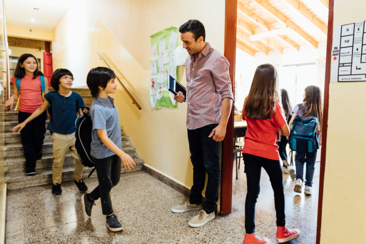 Teacher greets students. Image credit: iStock