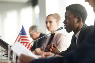 Young black man speaking on panel. Image credit: iStock